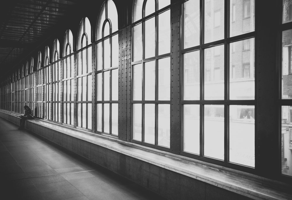 Photo by  Alex on  Unsplash    [Image Description: A black and white photograph of a hallway interior with large windows from the ceiling to the floor. A ledge protrudes from the base of the windows and person sits in the background.]