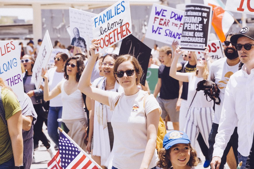 "[Photo description: a young white woman holds an American flag in one hand and in the other she raises a sign reading ""Families belong together"" above her head. A little girl marches beside her in a crowd of marchers]"