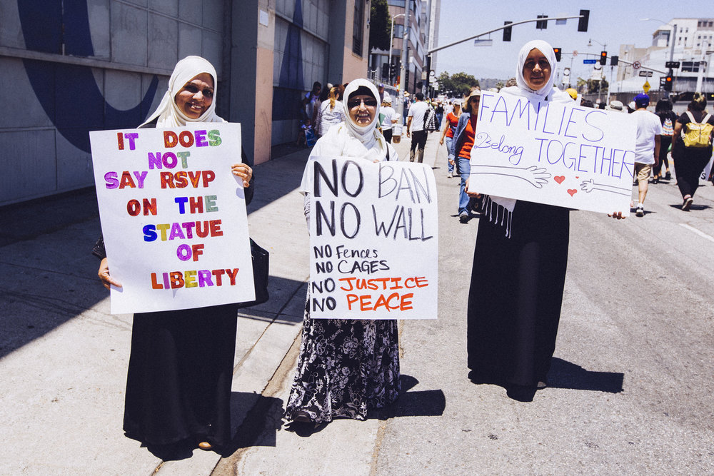 "[Photo description: Three young Muslim women in long skirts and white hijabs smile at the camera. They hold signs which read, respectively, ""It does not say RSVP on the statue of liberty,"" ""NO BAN NO WALL no fences no cages no justice no peace,"" and ""Families belong together.""]"