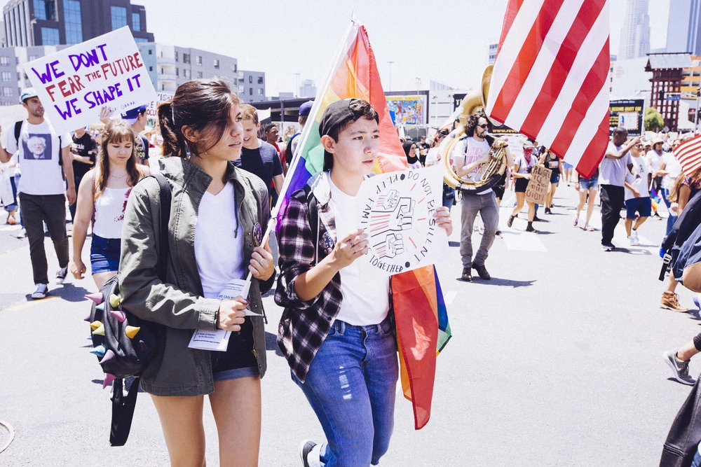 "[Photo description: A young Latina woman and a gender nonconforming person carry a rainbow flag and a sign that reads ""Keep families together. Do not be silent"" around a drawing of closed fists. Behind them, a different sign reads ""We don't fear the future, We shape it.""]"