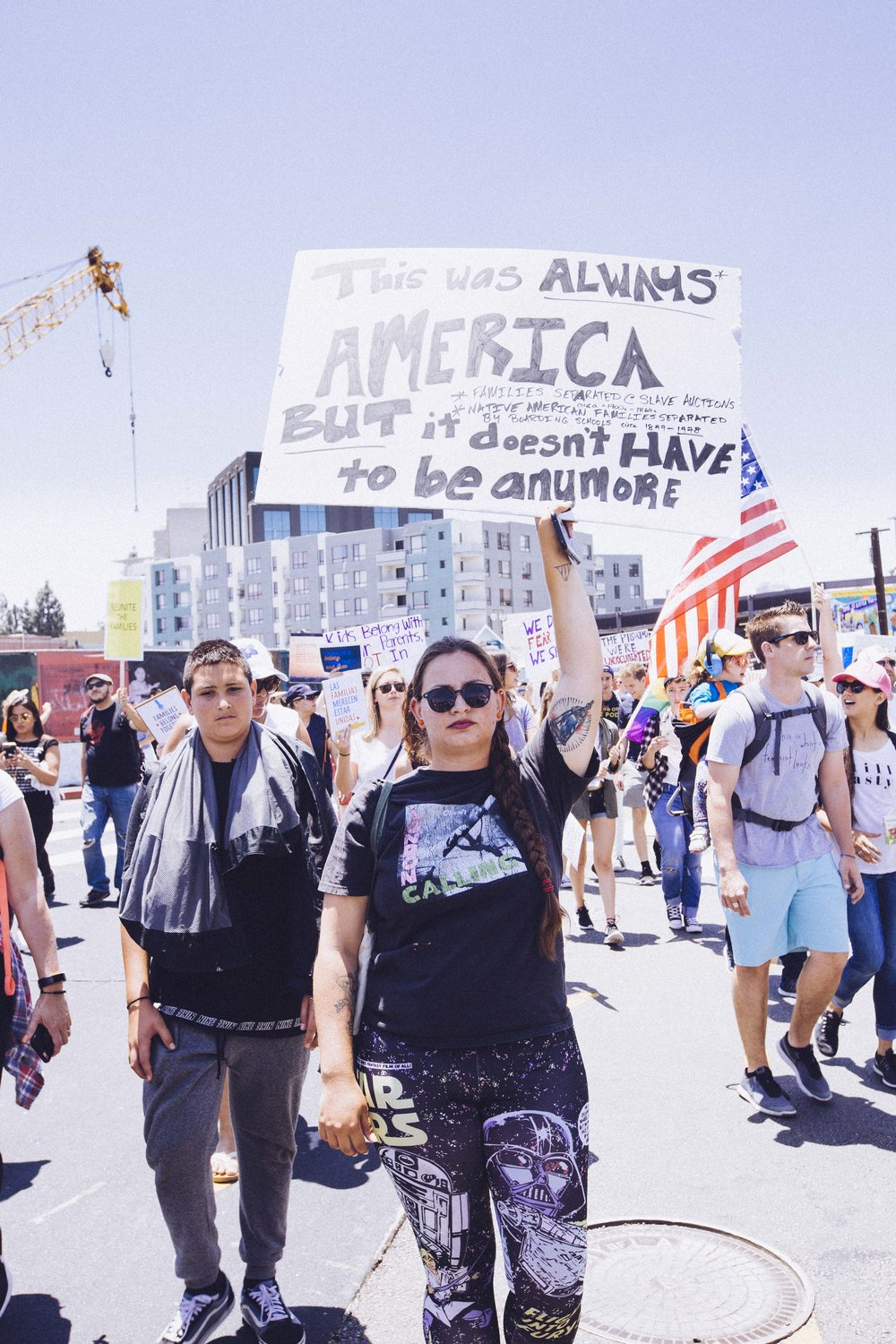 "[Photo description: a young, tattooed woman in Star Wars leggings scowls out of the crowd. She holds a sign reading ""This was always America. But it doesn't have to be anymore. *families separated @ slave auctions *Native American families separated by boarding schools circa 1840-1948""]"