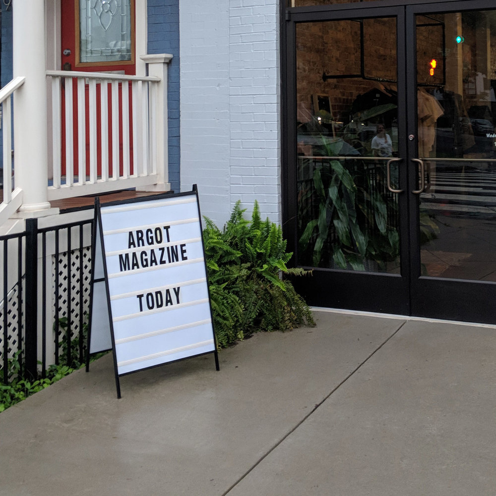 "Soph Bonde   [Image Description: Two glass doors are at the right of the photo, near the entrance of the building there is a bush and a sign that says ""Argot Magazine Today""]"
