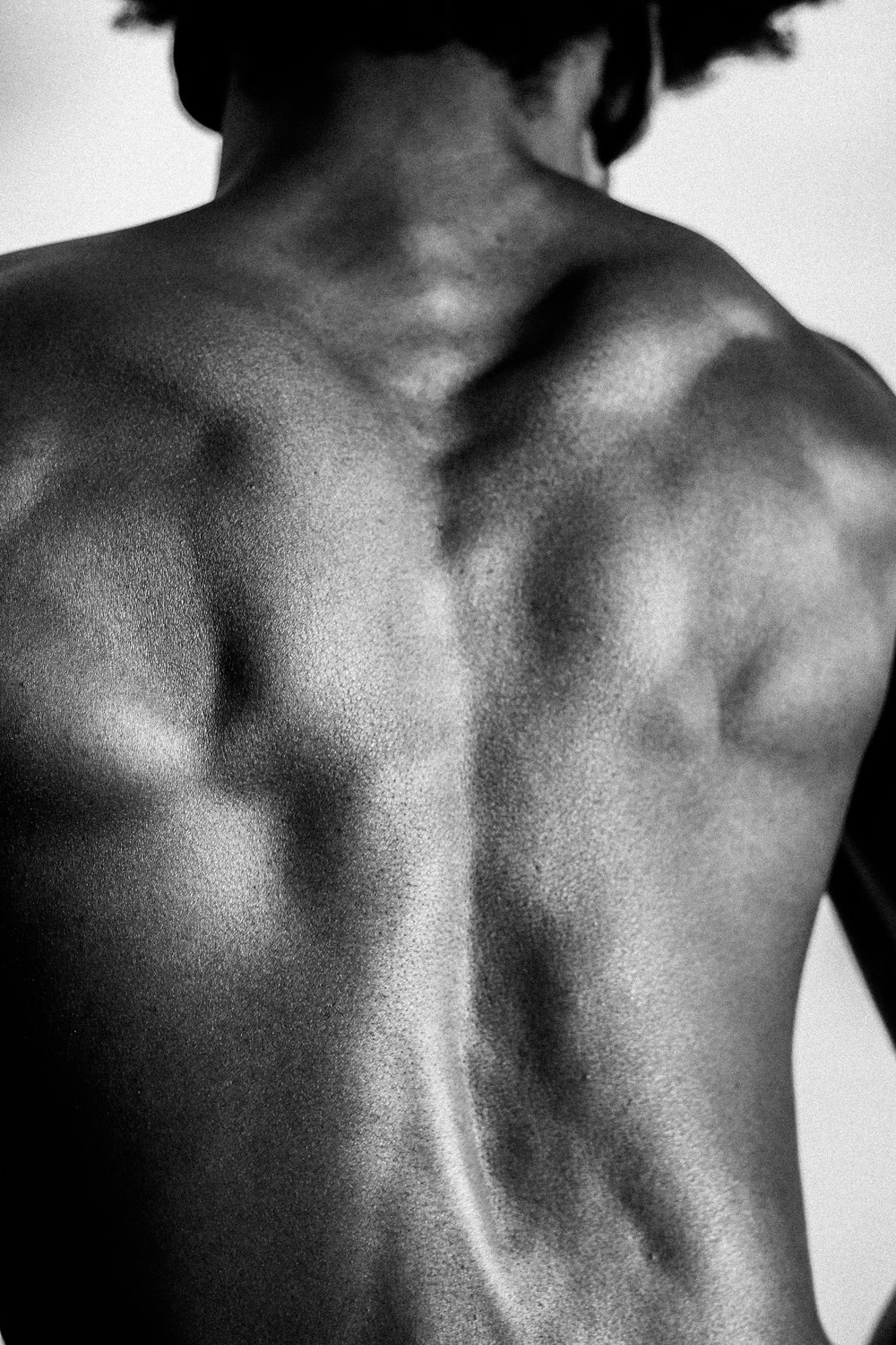 [Image Description: a black and white photo of the tensed mucscles and upper back and spine of a black man]
