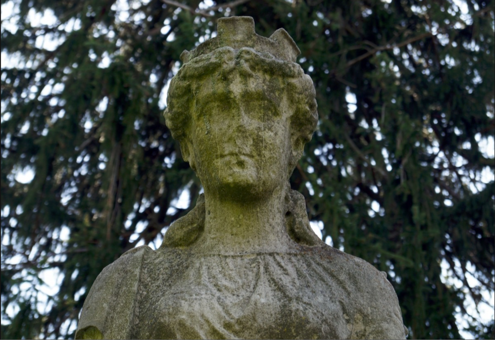 Creative Commons    [Image Description: The upper portion of an androgynous bust in a forest or garden, slightly overgrown with moss and features eroded]