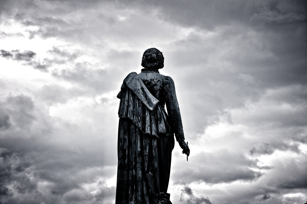Photo by  DAVIDCOHEN  on  Unsplash    [Image Description: A statued figure stands against the dark grey sky]