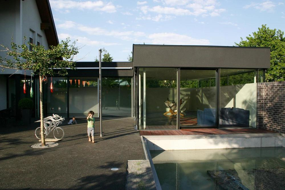 Context: a one-family-house in the countryside. The garden was unused-so space is left to situate an annexe to the existing house. The owners wished an additional living area and an outer space, which is achieved by an L-shaped building, forming a yard. Outside a pool connects to the annexe. The yard is surrounded by a 2m high wall of black exposed brickwork, which focuses the view to the surrounding hills. The neighbourhood is faded out and users only concentrate on life within the yard. The floor covering is black, perfectly harmonizing with the bricks and the terrazzo from inside the house.