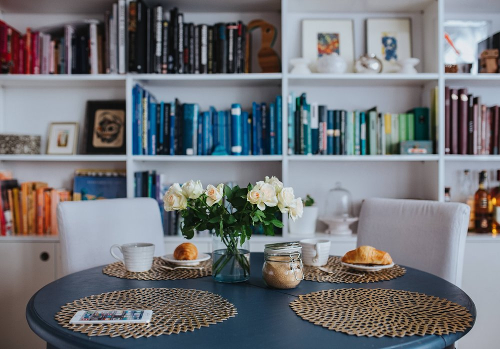 Round breakfast table with white flowers by the bookcase.jpg