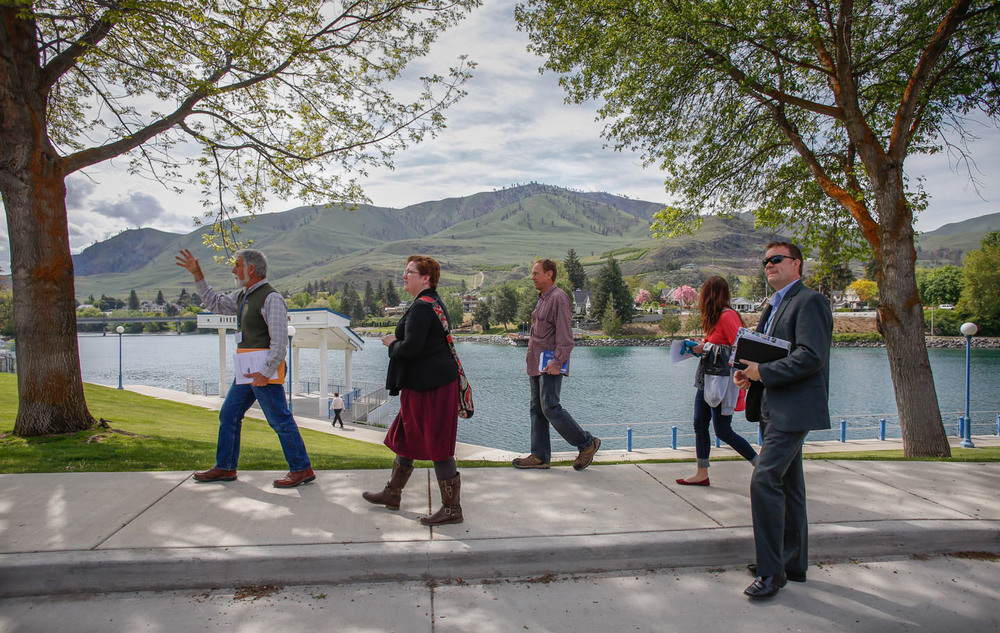"Chelan architect Larry Hibbard (far left) leads the ""Keeping Buildings Alive"" tour past Riverwalk Park with Chelan Butte in the distance. The recovering hills were blackened by the Reach fire less than a year ago."