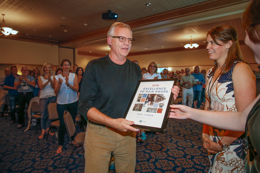Rory Turner, receives the 2016 Excellence on Main Award from  Breanne Durham and Jennifer Mortensen  for his preservation and restoration work of the Elks Lodge in   Ellensburg, WA.