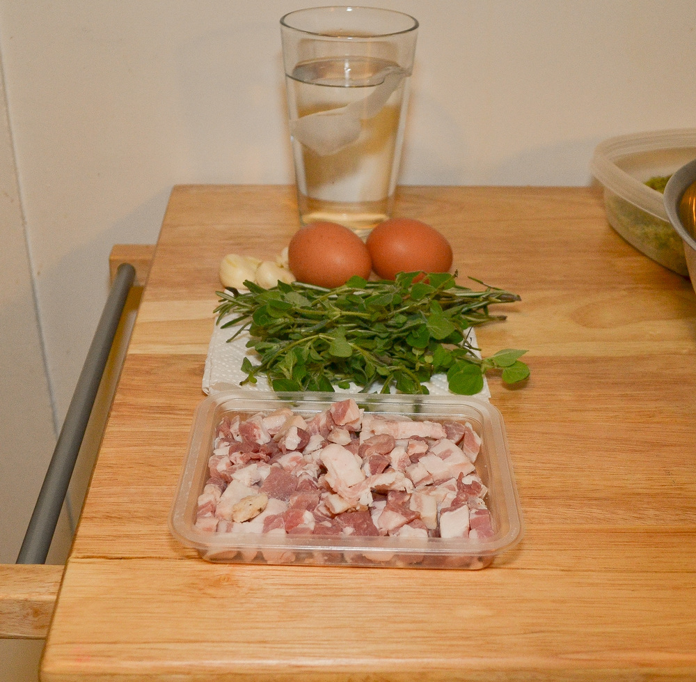 (from front to back) Pancetta, fresh oregano & rosemary, peeled garlic cloves, cage free eggs & ice water