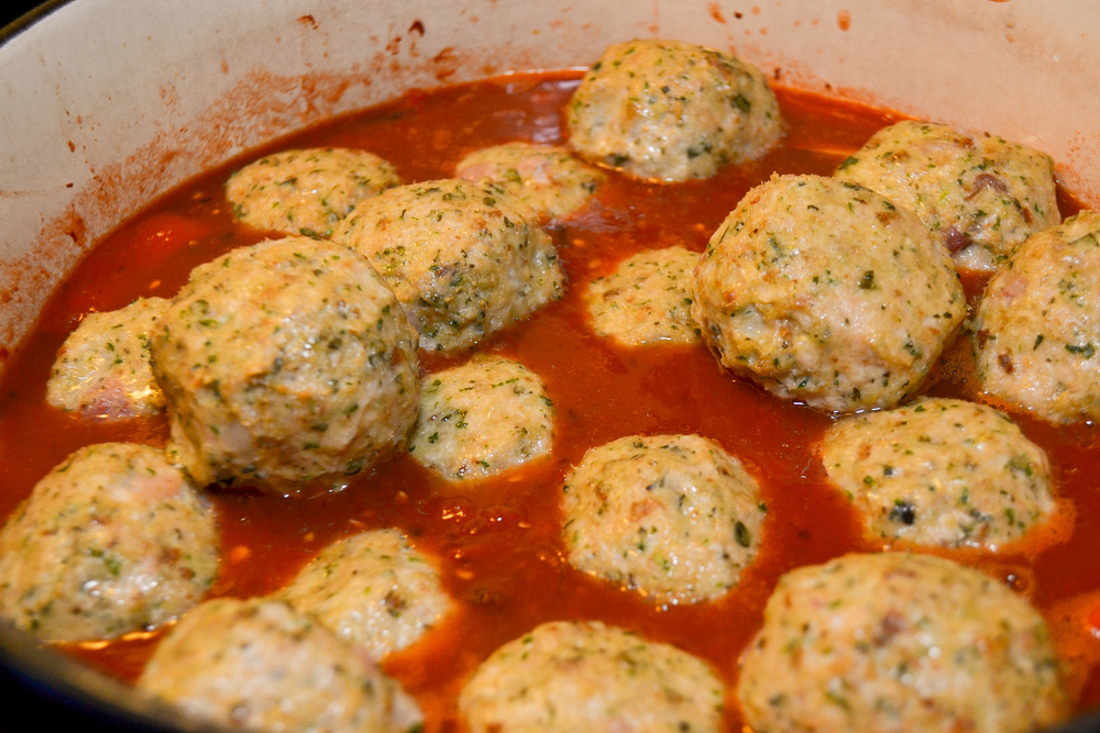 Meatballs dropped into sauce