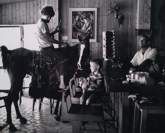 Ron's father (behind the bar), brother (on the toy horse) and Musmas, a drug-dealing mafia Israeli cowboy.
