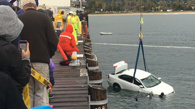 Car being hoisted by crane with assistance of diving crew