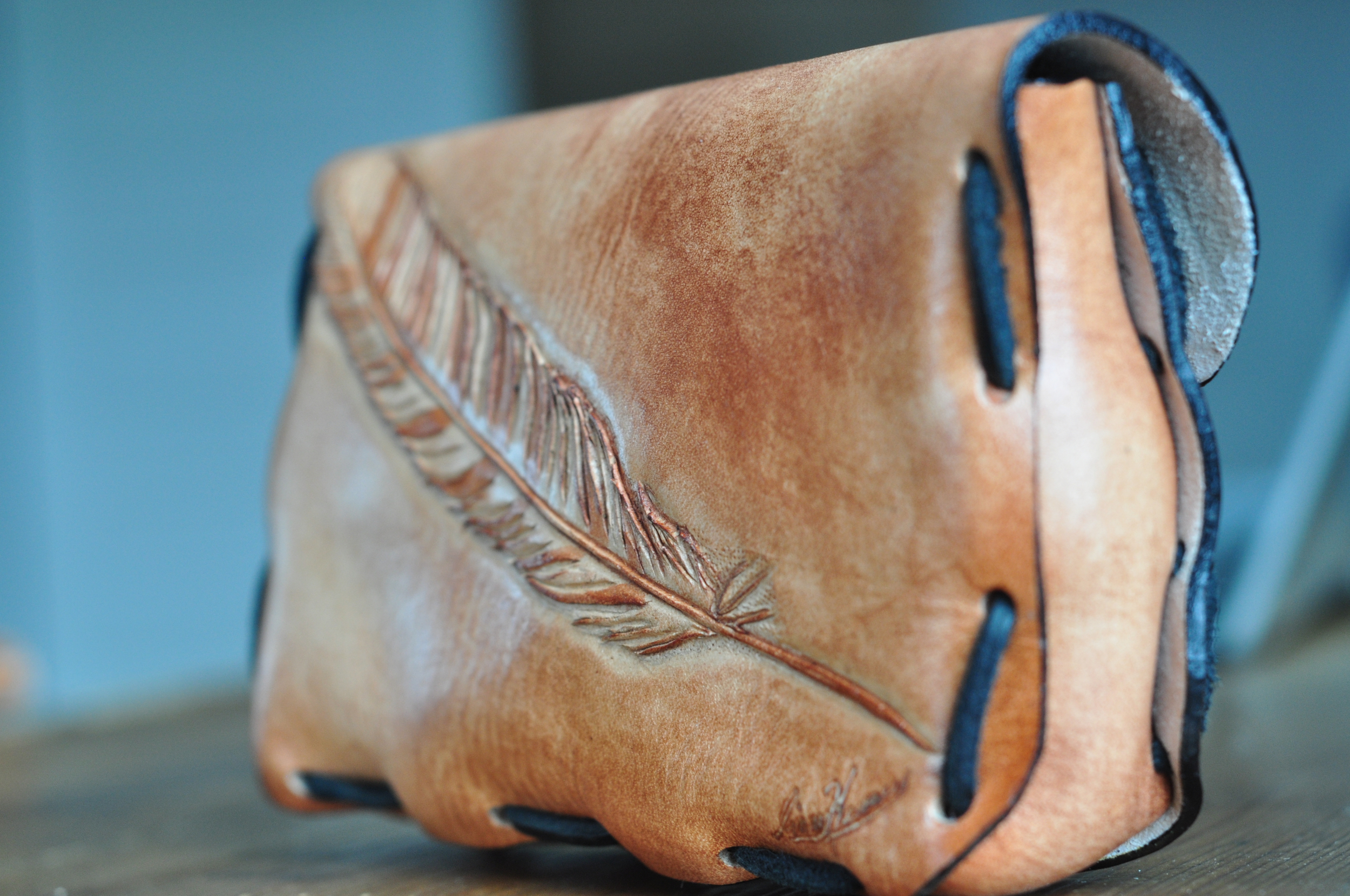 small leather clutch with tooled feather-