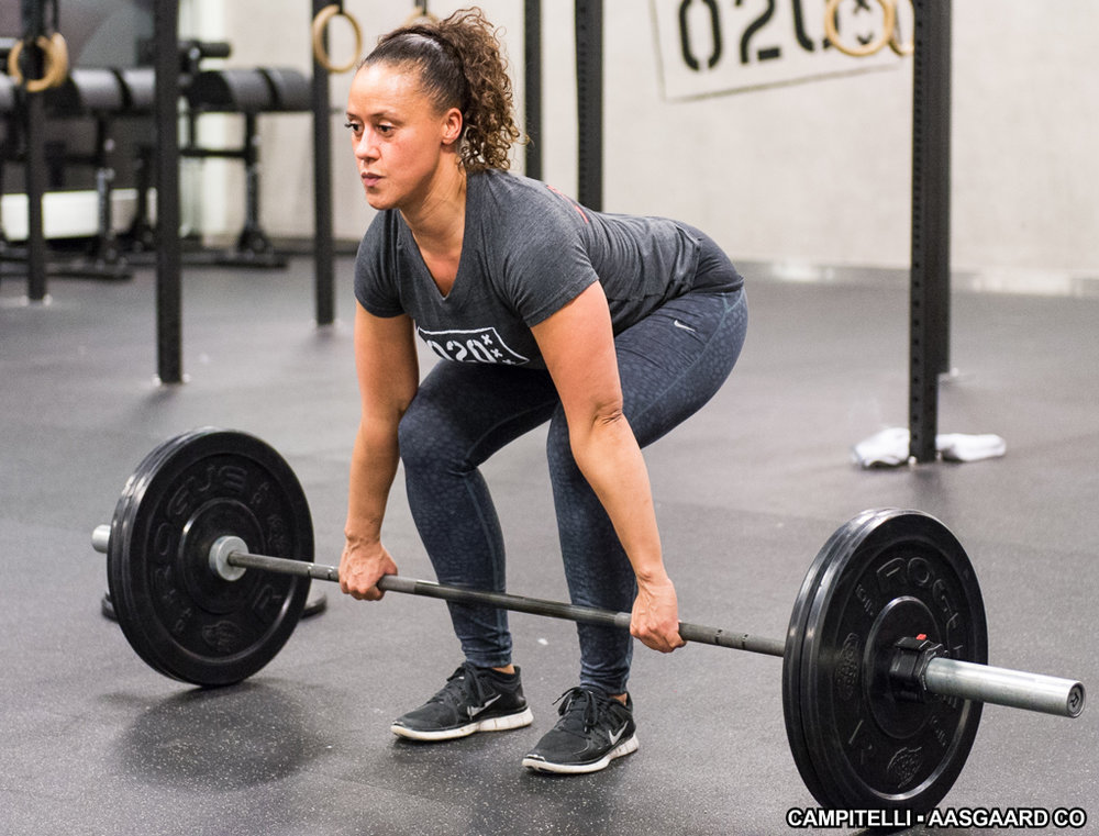 This athlete demonstrates the typical thoracic extension utilized in a deadlift. Though we do not want to see her low back round, I would like to see her pull her ribs down in the front while still kicking on her lats and keeping the bar close.