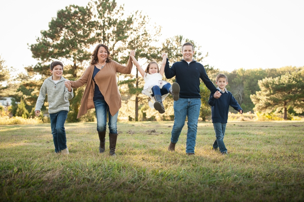 family of five swinging little girl in field | huntsville family photographer