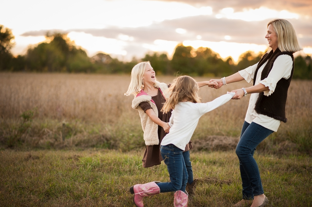 mom and two daughters twirling in grass - huntsville family photography