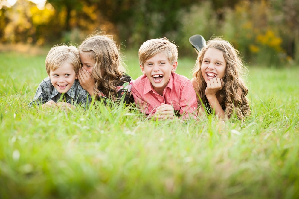 four siblings laughing in grass - huntsville child photographer