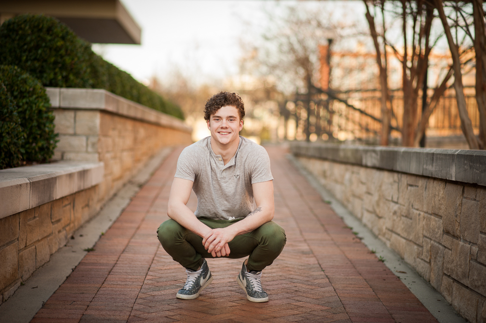 graduating guy squatting {huntsville al senior portraits}