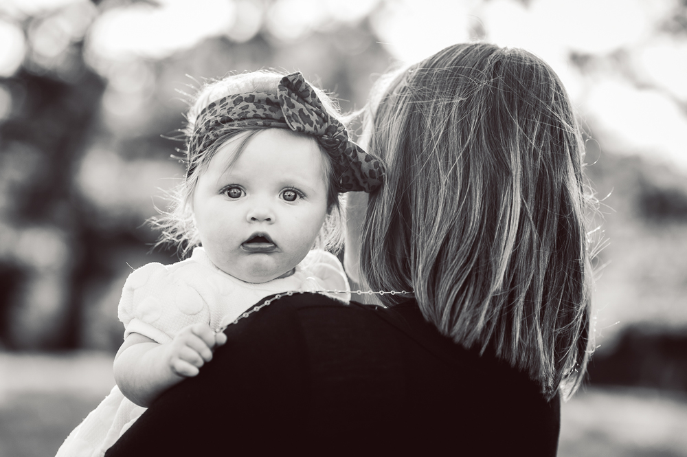 6-month-old girl peeking over mom's shoulder - huntsville baby photographer