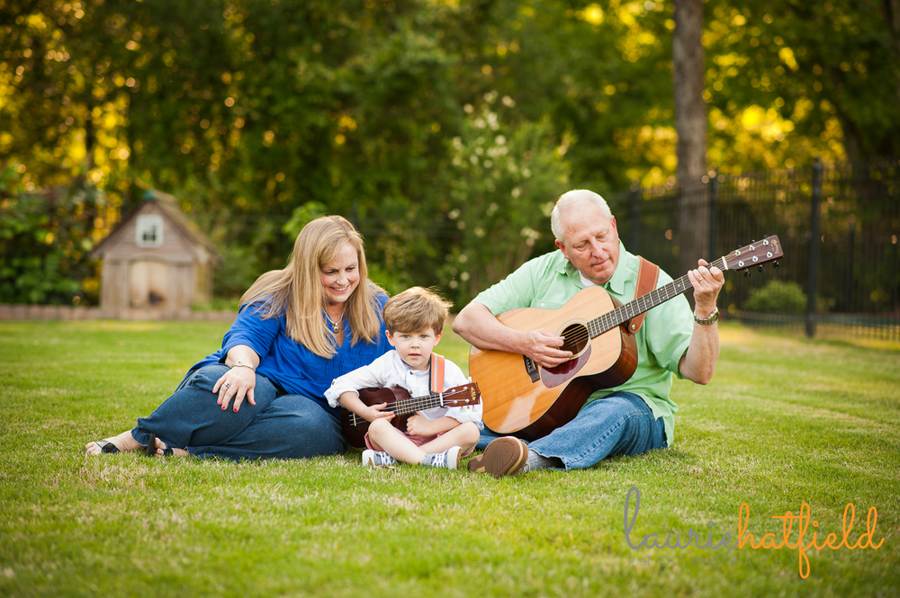 grandparents and grandson playing guitar in grass | Huntsville family photographer