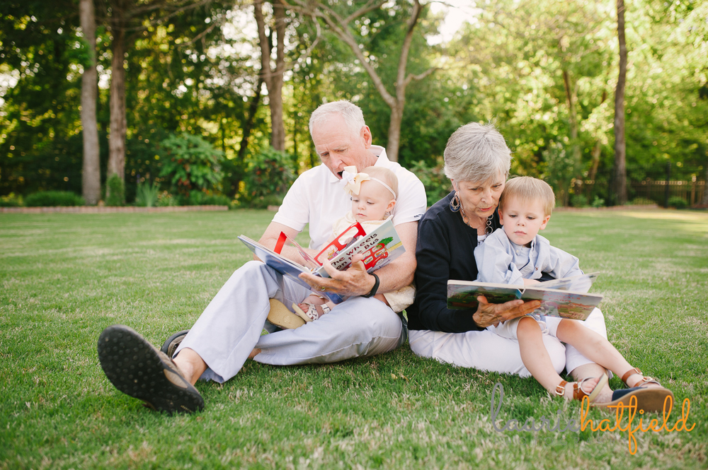 grandparents reading on lawn with grandchildren | Huntsville family photographer
