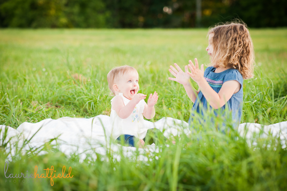 sisters clapping in grass | Huntsville family photographer