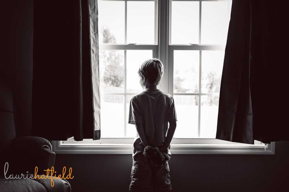 little boy standing at window holding stuffed animal | Huntsville child photographer