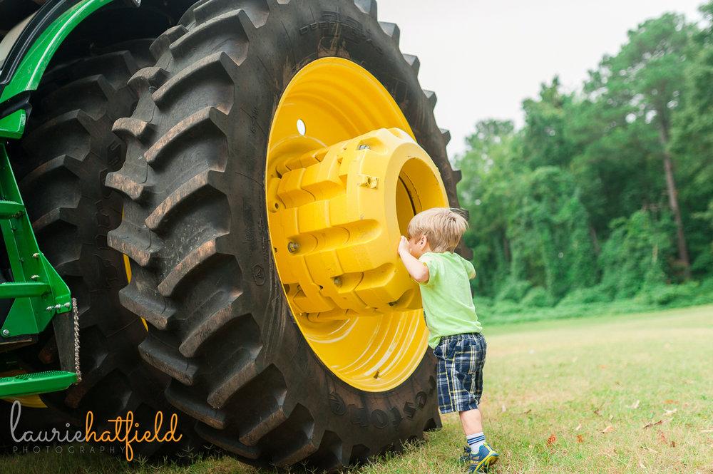 little boy peering into tractor tire | Huntsville photographer