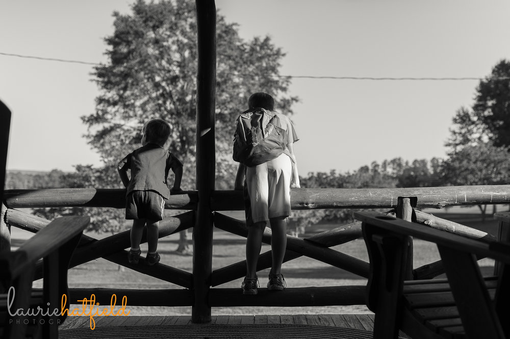 2 brothers looking over porch of cabin | Huntsville family photographer