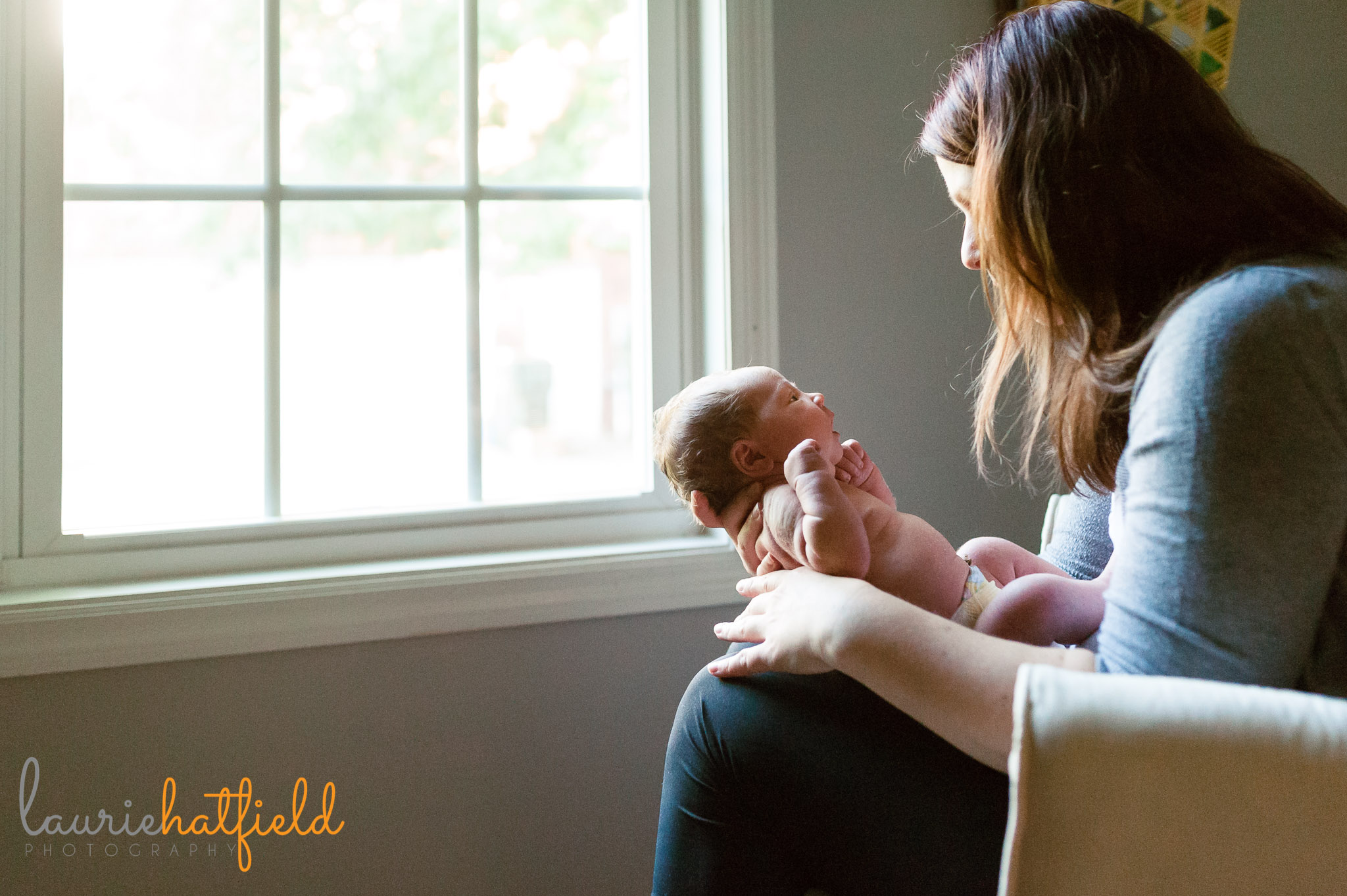 mom and newborn baby girl by window | Mobile AL lifestyle photographer