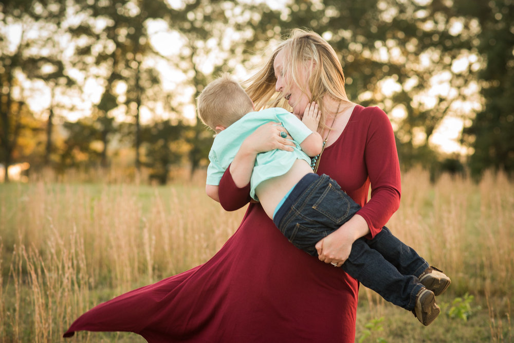 mom twirling with son in grass | Mobile family photographer