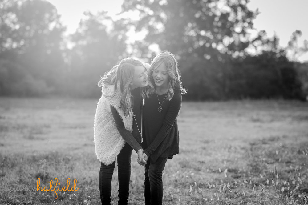 sisters laughing in a field | Mobile family photographer