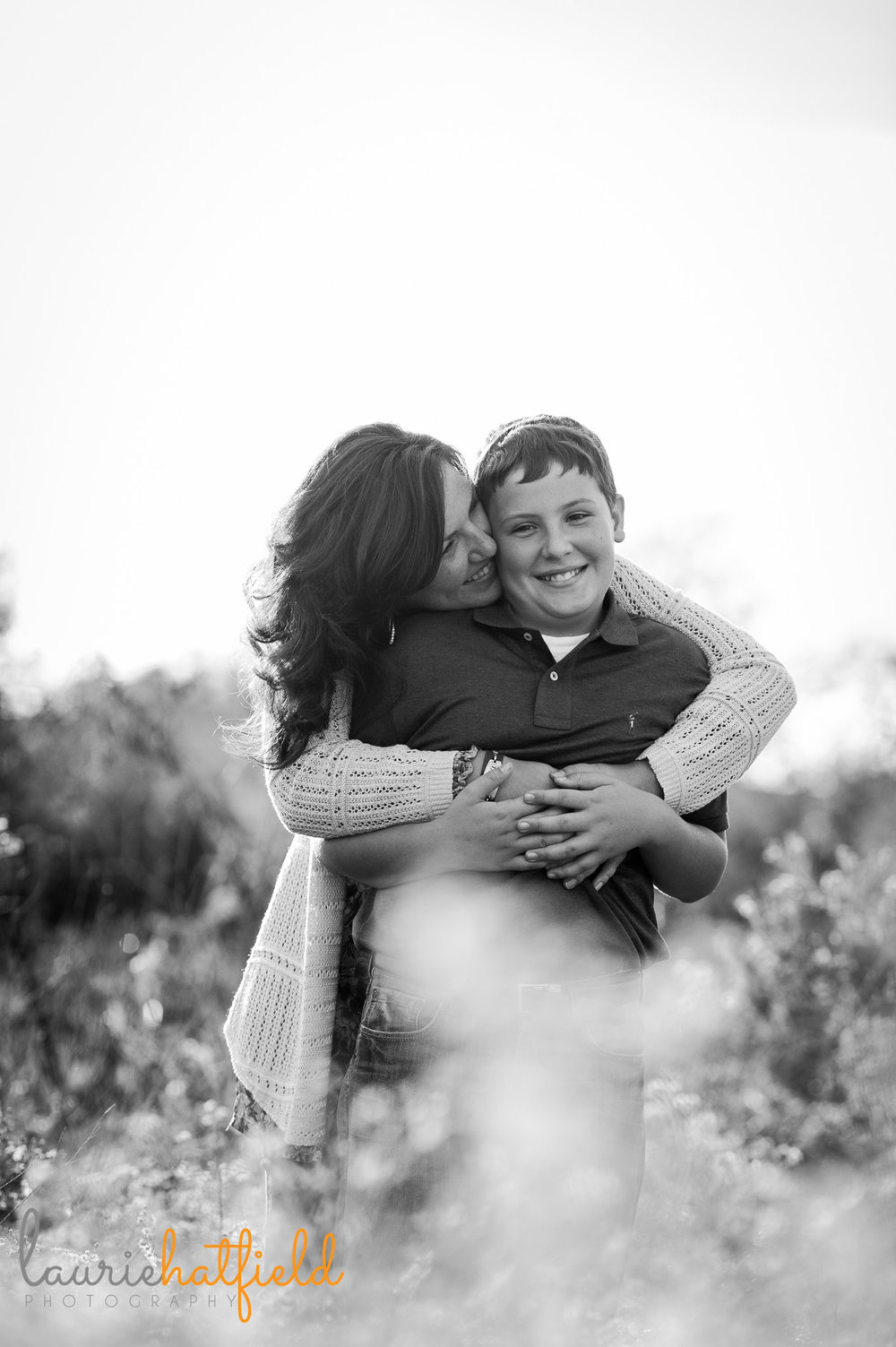 mom hugging son in field | Mobile family photographer