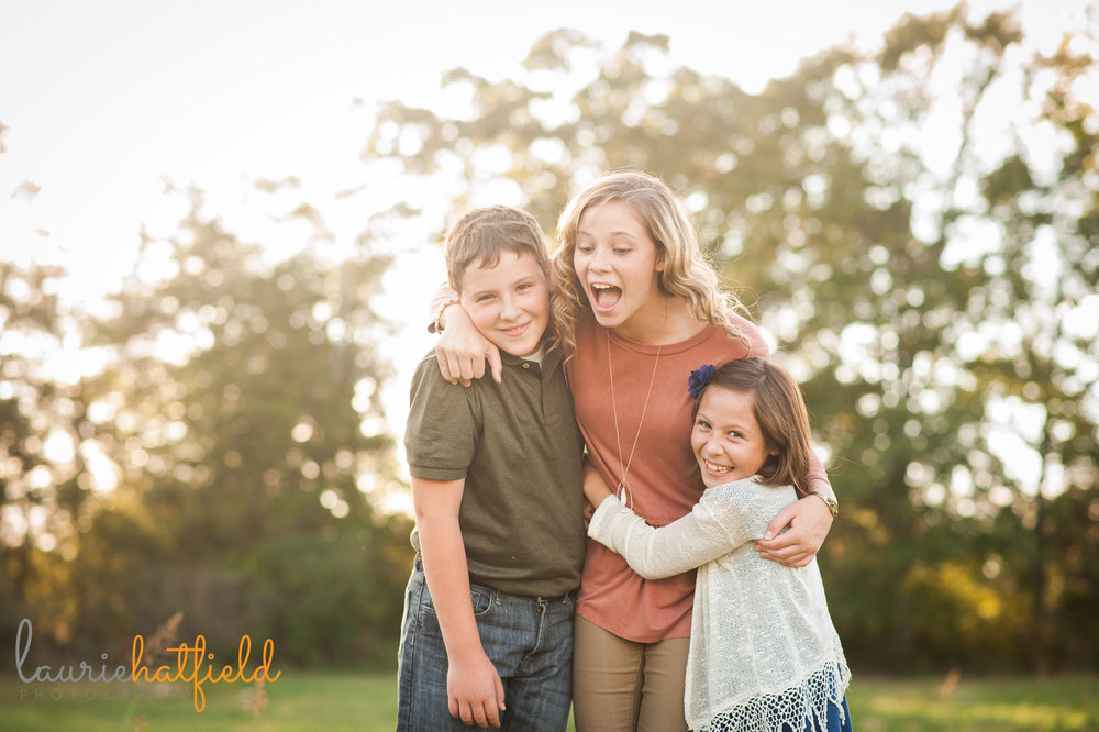brother and 2 sisters laughing in a field | Mobile child photographer