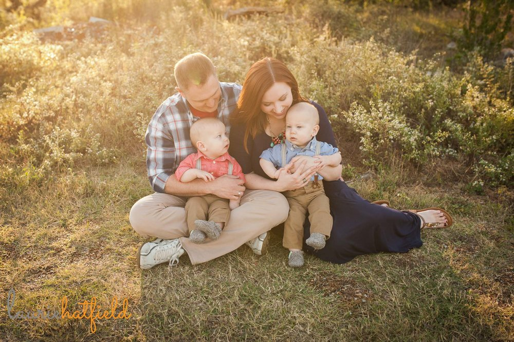 family with twin babies sitting in grass
