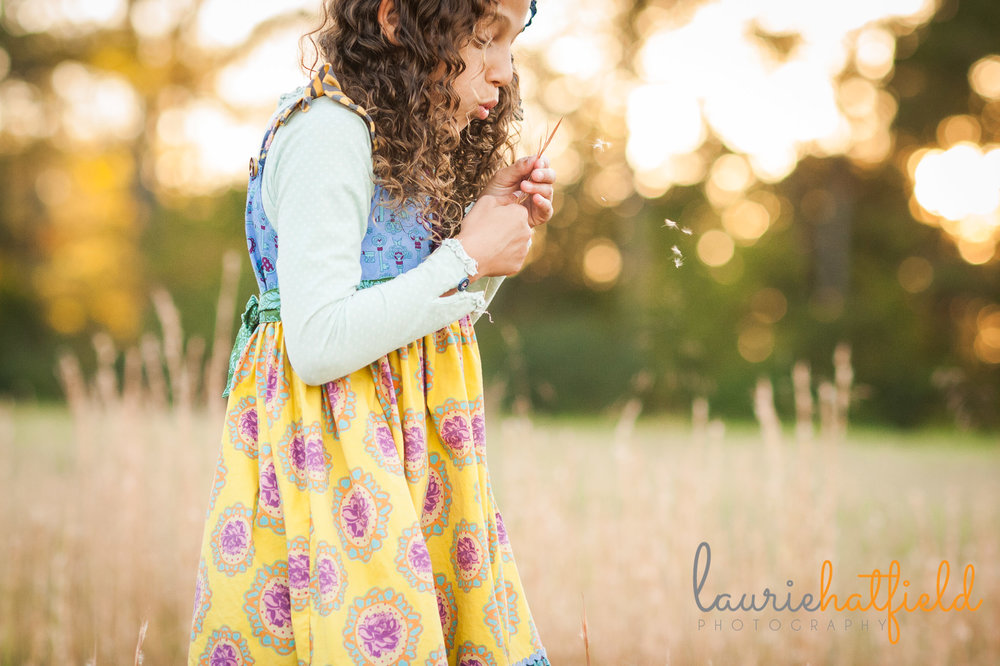 little girl blowing dandelions in field | Laurie Hatfield Photography | Mobile AL family photographer