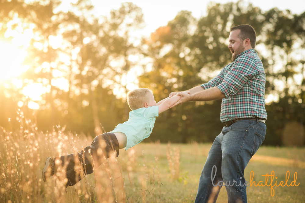 dad swinging little boy around in a field | Mobile AL family photographer