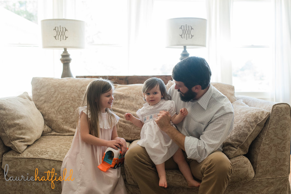 dad with 2 daughters on sofa | Mobile lifestyle newborn photographer