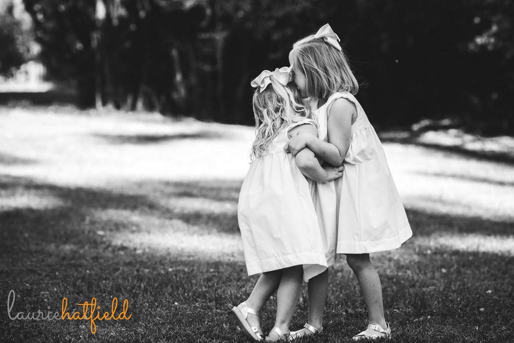 two sisters whispering in black and white by Mobile family photographer Laurie Hatfield Photography