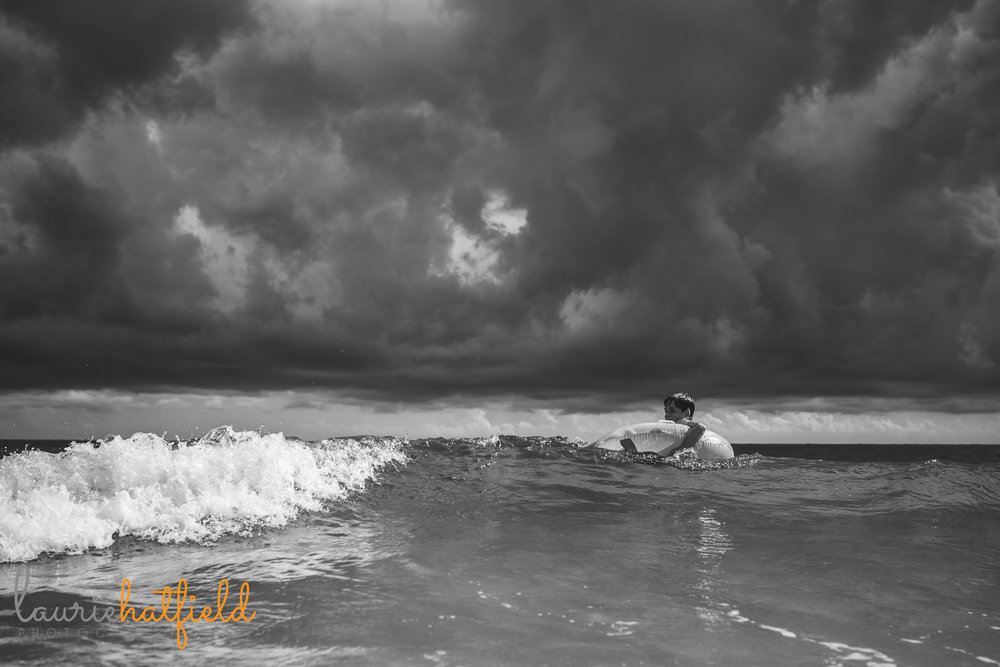 boy on float in ocean with clouds above | Mobile AL child photographer