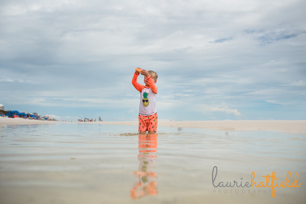 little boy playing with a boat on the beach | Mobile AL family photographer