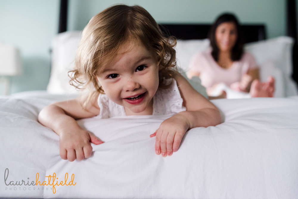 2-year-old girl playing on bed | Mobile AL newborn photographer
