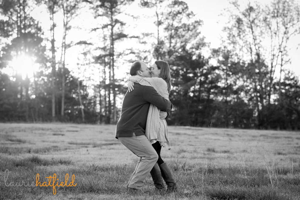 couple embracing in field | Mobile AL lifestyle family photographer