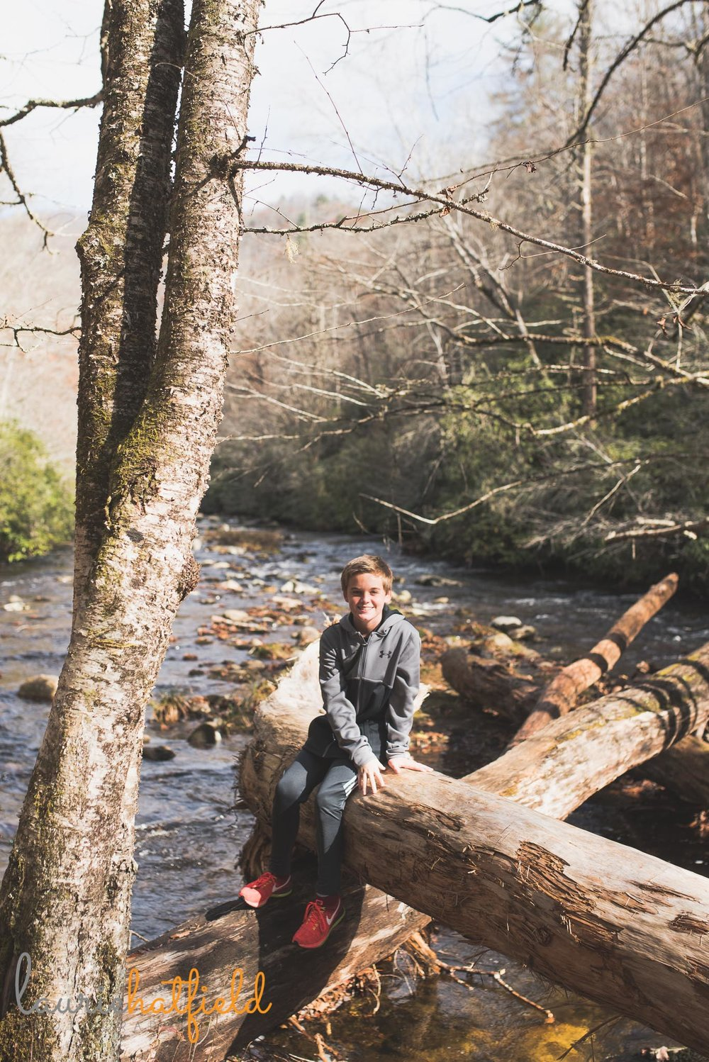 boy sitting on log over river | Mobile al family photographer