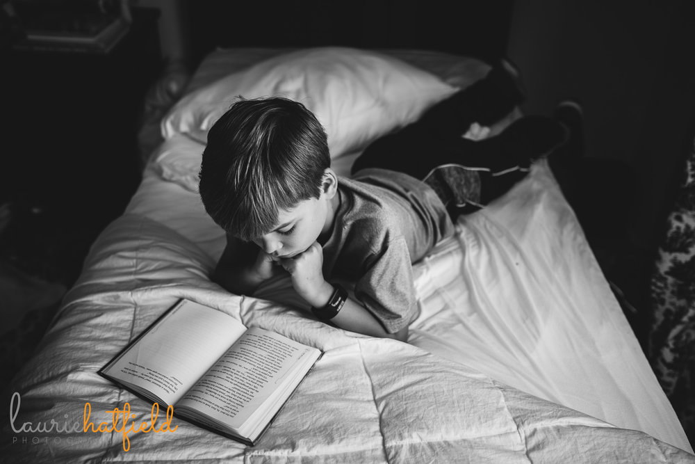 black and white image of little boy reading on bed | Mobile AL family photographer