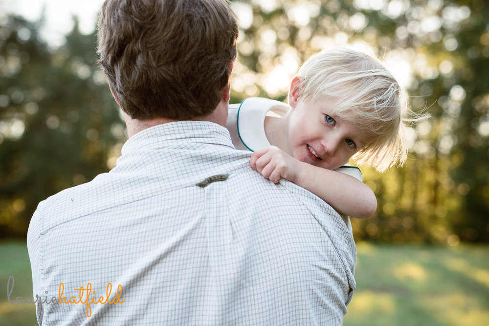 little boy peeking over dad's shoulder | Fairhope AL family photographer