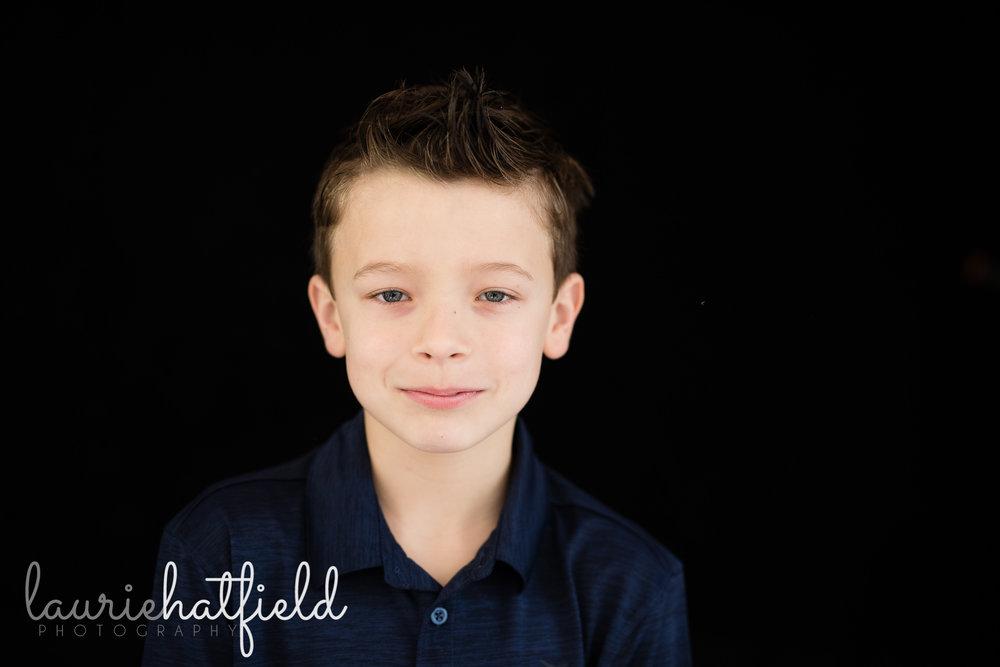 boy in blue shirt against black backdrop | Mobile AL school portrait photography