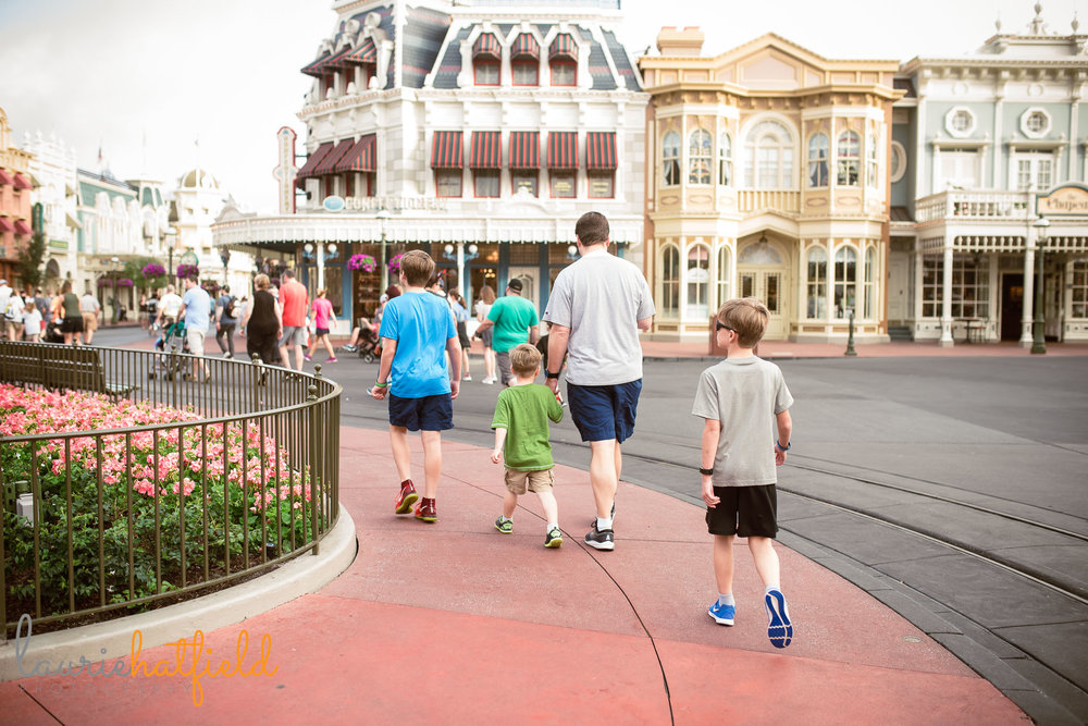 dad and boys walking in Magic Kingdom | Mobile AL family photographer