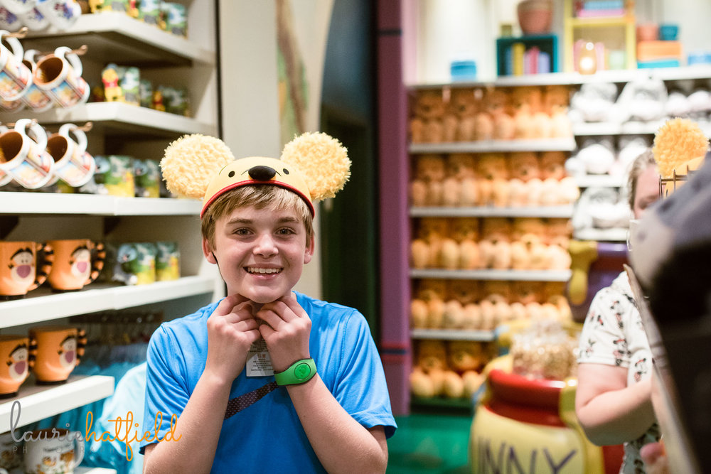 boy trying on Pooh bear hat | Mobile AL family photographer